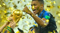 France's Hugo Lloris lifts the trophy as Kylian Mbappe with team mates celebrate winning the World Cup