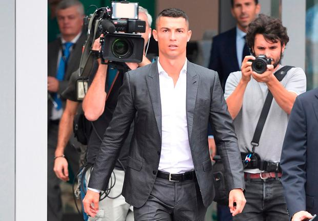 TOPSHOT - Portuguese footballer Cristiano Ronaldo (C) arrives on July 16, at the Juventus medical center at the Alliance stadium in Turin. Miguel MEDINA/AFP/Getty Images