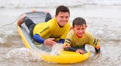 Callum (12) and his brother Leighton (9) Dempsey from Arklow enjoy the surf in Brittas Bay. Photo: Damien Eagers
