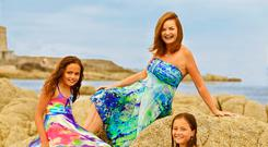 Denise Moroney pictured with her twin daughters, Sophie and Daniella (11) wearing 'Sophie Sarongs'. From left: Sophie wears 'Purple Sky' print, €99, Denise wears 'Waterfall', €149 and Daniella wears 'Dufy Pomegranate', €99; All available from sophiesarongs.com