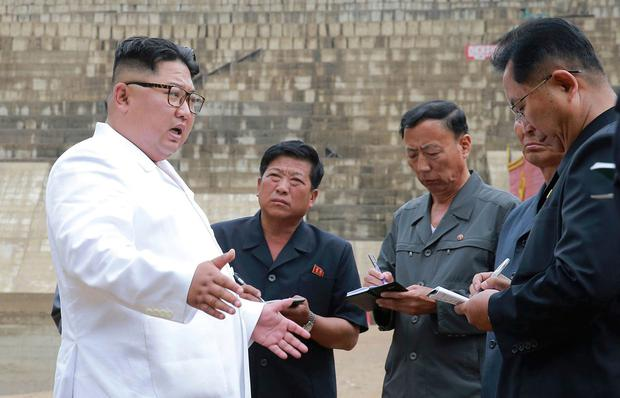 North Korean leader Kim Jong-un speaks to officials as he inspects the construction site of a hydroelectric power plant in North Hamgyong Province. Photo: AP
