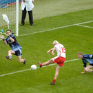 Owen Mulligan, Tyrone, shoots past Stephen Cluxton in the Dublin goal to score his side's second goa in 2005
