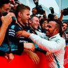 Mercedes' Lewis Hamilton celebrates winning the race with team members. Photo: Reuters