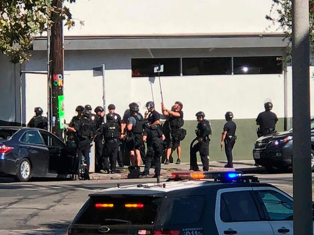 Police use a mirror to see inside the Trader Joe's store during the three-hour siege. Photo: Christian Dunlop via AP