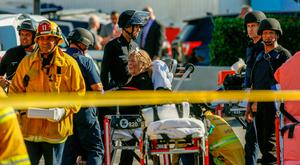 A woman is helped by paramedics after she was held hostage. Photo: AP