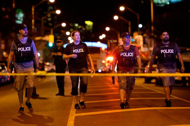 Plainclothes police officers work the scene of shooting in Toronto on Sunday, July 22, 2018. (Nathan Denette/The Canadian Press via AP)