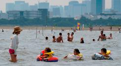 Families swim and play in the water at a seaside park in Tokyo on July 22, 2018. AFP PHOTO / Kazuhiro NOGI/AFP/Getty Images