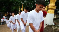 Soccer coach Ekkapol Chantawong, front, and members of the rescued soccer team arrive to attend a Buddhist ceremony in Mae Sai district, Chiang Rai province, northern Thailand, Tuesday, July 24, 2018. (AP Photo/Sakchai Lalit)