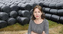 Farmer Claire Spencer with bales of hay on her family farm in Annahala, Co Cork. Photo: Daragh McSweeney