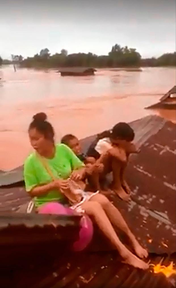 Screen grab taken on handout video footage from ABC Laos on July 24, 2018 shows people sitting on a rooftop of a house surrounded by floodwaters in Attapeu province after a dam collapsed the day before. AFP PHOTO / ABC LAOS