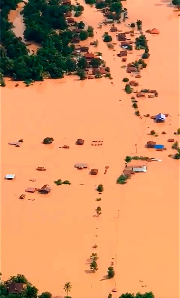 This screen grab taken on handout video footage from ABC Laos on July 24, 2018 shows an aerial view of the flooded plains in Attapeu province after a dam collapsed the day before. AFP PHOTO / ABC Laos