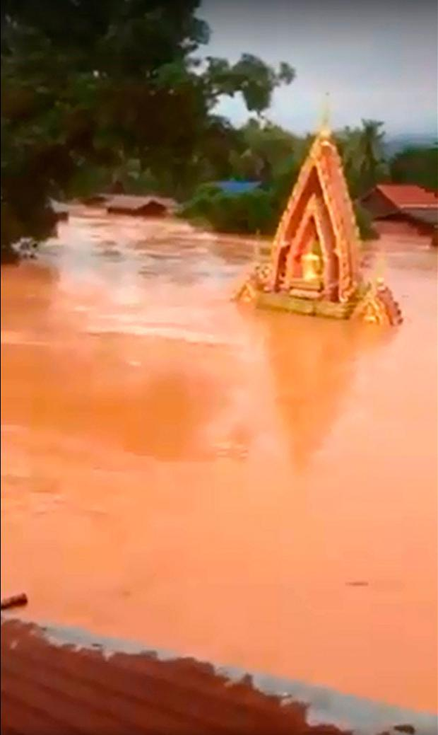 This screen grab taken on handout video footage from ABC Laos on July 24, 2018 shows various structures surrounded by floodwaters in Attapeu province after a dam collapsed the day before. AFP PHOTO / ABC LAOS.