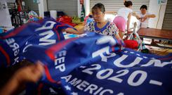 Workers make flags for US President Donald Trump's