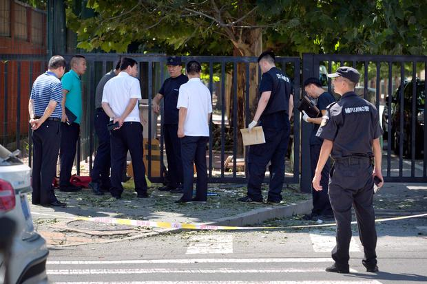Officials and security personnel stand near the site of reported blast just south of the U.S. Embassy in Beijing (AP Photo/Mark Schiefelbein)