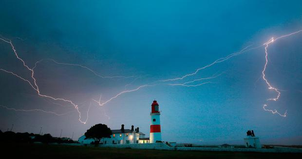 Lightning flashes over Souter lighthouse in South Shields. Photo: Owen Humphreys/PA Wire