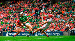Limerick's Aaron Gillane kicks over a point as Cork goalkeeper Anthony Nash rushes out. Gillane was the semi-final's outstanding forward, finishing with five points from play. Photo by Ramsey Cardy/Sportsfile