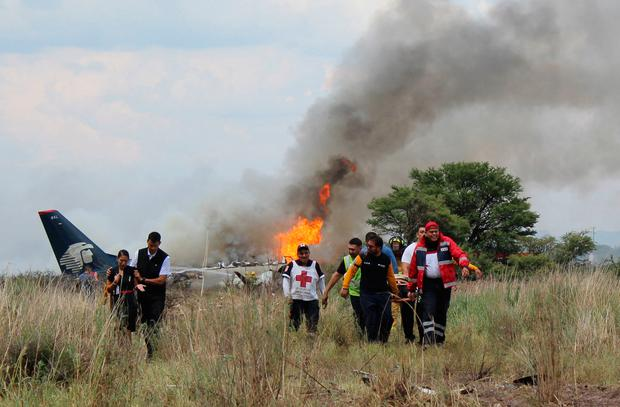 In this photo released by Red Cross Durango communications office, Red Cross workers and rescue workers carry an injured person on a stretcher, right, as airline workers, left, walk away from the site where an Aeromexico airliner crashed in a field near the airport in Durango, Mexico (Red Cross Durango via AP)