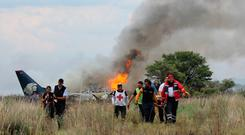 In this photo released by Red Cross Durango communications office, Red Cross workers and rescue workers carry an injured person on a stretcher, right, as airline workers, left, walk away from the site where an Aeromexico airliner crashed in a field near the airport in Durango, Mexico, Tuesday, July 31, 2018. The jetliner crashed while taking off during a severe storm, smacking down in a field nearly intact then catching fire, and officials said it appeared everyone on board escaped the flames. (Red Cross Durango via AP)