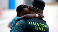 A Spanish Civil Guard holds a migrant child, intercepted in the Strait of Gibraltar. Photo: REUTERS/Jon Nazca