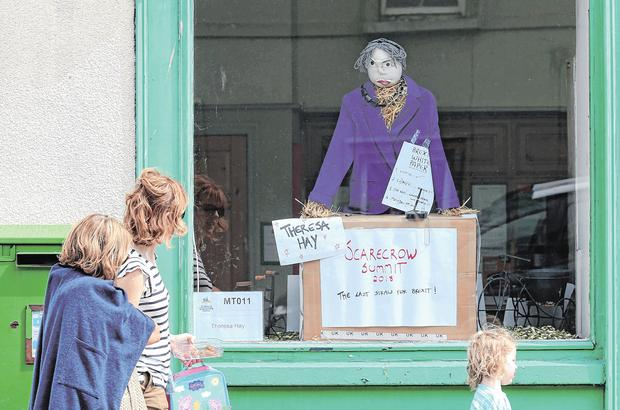 Passers-by look at a Brexit-themed display titled 'Theresa Hay' on display in the post office in Durrow, Co Laois, as part of the annual Scarecrow Festival, which runs until this weekend. Photo: Laura Hutton