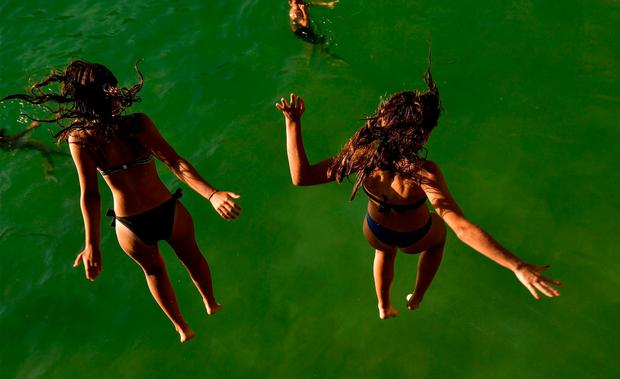 Two women jump from a platform over the water at La Concha beach during a hot summer day in the basque city of San Sebastian, northern Spain