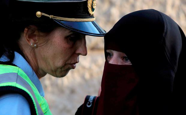 A police officer speaks with Ayah, 37, during a demonstration against the Danish face veil ban in Copenhagen. REUTERS/Andrew Kelly