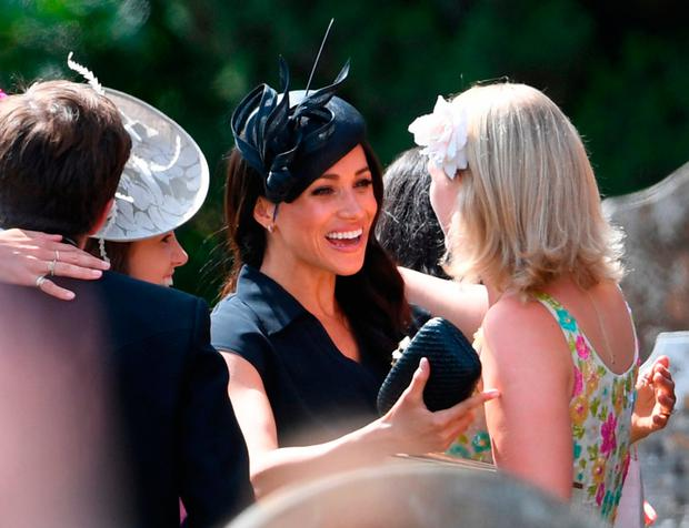 The Duchess of Sussex (centre) talks to fellow guests as they arrive to attend the wedding of Charlie van Straubenzee and Daisy Jenks at St Mary the Virgin Church in Frensham, Surrey. PRESS ASSOCIATION Photo. Picture date: Saturday August 4, 2018. See PA story ROYAL Sussex. Photo credit should read: Joe Giddens/PA Wire