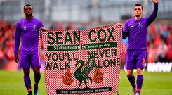 Georginio Wijnaldum, left, and Andy Robertson of Liverpool hold a banner in support of Liverpool supporter Sean Cox