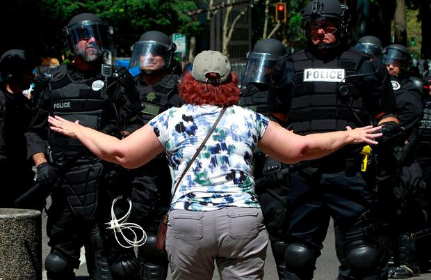 A counter-protester argues with police during a rally by the Patriot Prayer group in Portland, Oregon, U.S. August 4, 2018. REUTERS/Bob Strong