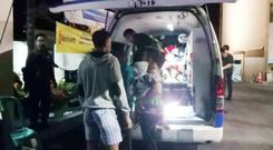 People are seen next to the ambulance near the Golden Palace Hotel after an earthquake hit Lombok Island, Indonesia