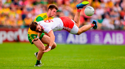 Tyrone's Padraig Hampsey goes flying under pressure from Eoghan Bán Gallagher at MacCumhaill Park. Photo by Stephen McCarthy/Sportsfile