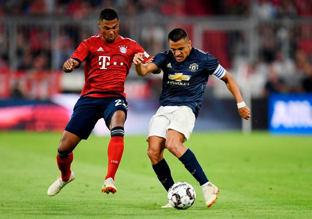 Manchester United's Alexis Sanchez in action with Bayern Munich's Serge Gnabry. Photo: Andreas Gebert/Reuters