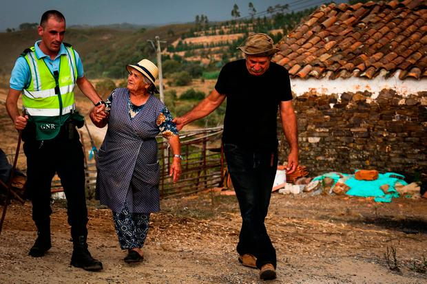 police officer evacuates locals due to a wildfire close to Monchique in the Algarve. Photo: AFP/Getty Images