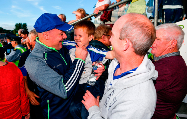 Monaghan manager Malachy O'Rourke celebrates with Paudie McCarey, aged 5, and his father Joe McCarey, from Gaeil Triucha, Co. Monaghan