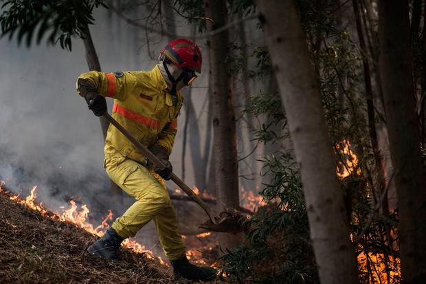 A firefighter works on an active fire on a hillside outside the village of Monchique, in southern Portugal's Algarve region, Monday, Aug. 6, 2018. (AP Photo/Javier Fergo)