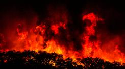 Large flames are seen on a hillside outside the village of Monchique, in southern Portugal's Algarve region, Sunday, Aug. 5 2018. (AP Photo/Javier Fergo)