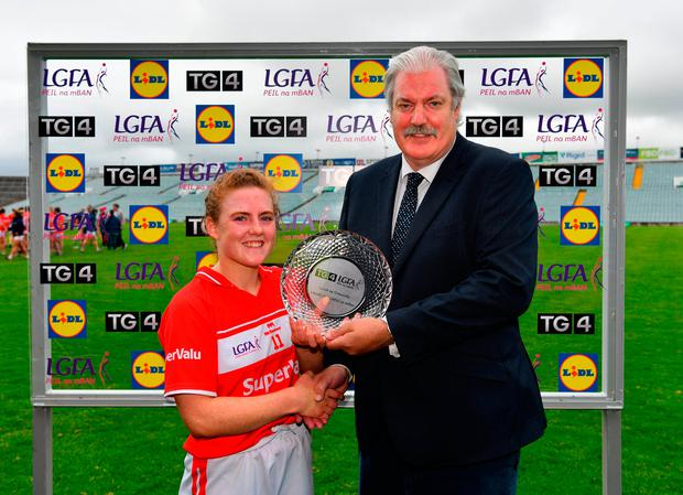 Cork's Libby Coppinger is presented with the Player of the Match award by Dominic Leech, President, LGFA Leinster Branch. Photo: Diarmuid Greene/Sportsfile