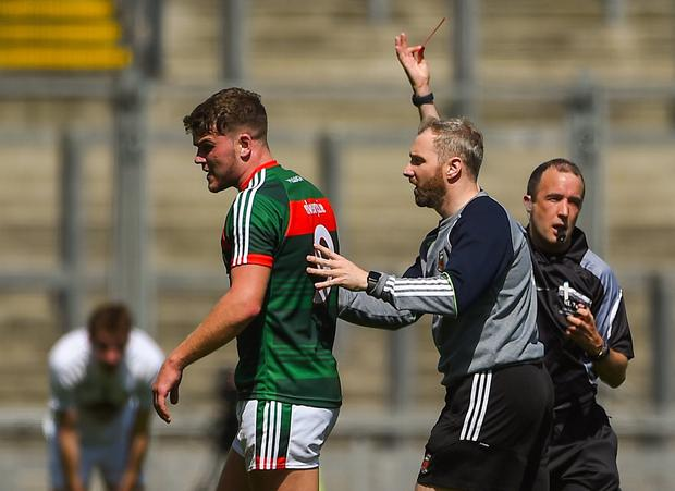 Jordan Flynn is escorted off the pitch after receiving a red card from referee Niall Cullen. Photo: Daire Brennan/Sportsfile