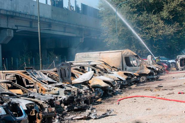 A firefighter sprays water among charred vehicles under the highway in the outskirt of Bologna, Italy, after a tanker truck carrying flammable material exploded, killing at least two people and injuring up to 70 as it partially collapsed the overpass. Giorgio Benvenuti/ANSA via AP