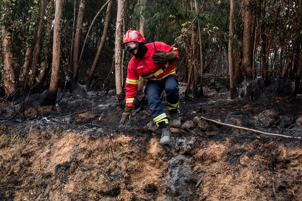 A firefighter jumps off a small mound while working on a fire near the village of Monchique, in southern Portugal's Algarve region, Monday, Aug. 6, 2018. (AP Photo/Javier Fergo)