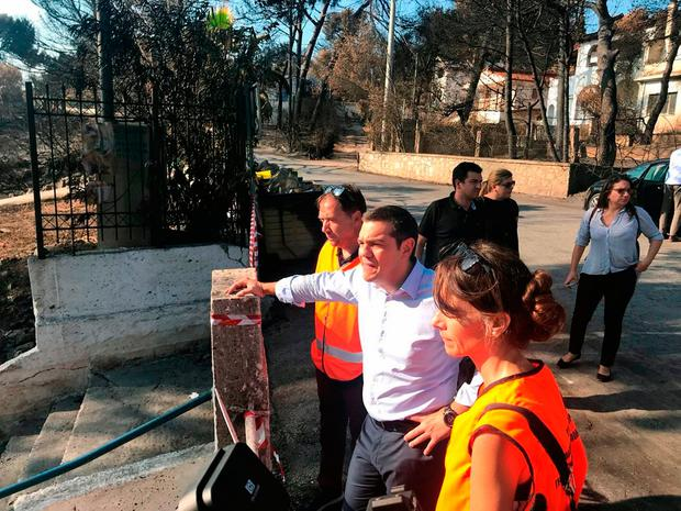 Greece's Prime Minister Alexis Tsipras, front centre, tours the burnt area of Mati, east of Athens, last week. Photo: AP