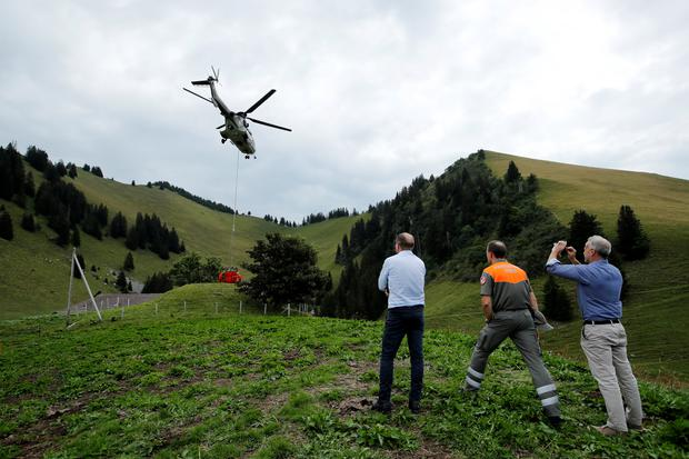 A Swiss Air Force Super Puma helicopter delivers water for cows in a pasture due to an ongoing drought near Rossiniere, Switzerland, August 7, 2018. REUTERS/Denis Balibouse