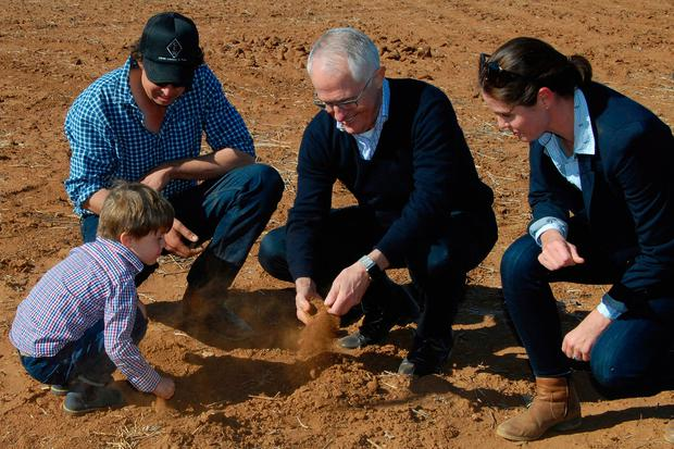 Australian Prime Minister Malcolm Turnbull, second right, looks at dry soil with farmers during a visit to Strathmore Farm near Trangie, 300 miles north west of Sydney. Photo: Ivan McDonnell/AP