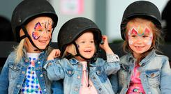 Sisters Isla (4), Georgia (2) and Sophia McCormack (6) from Nass have fun as they wait their turn for a Pony ride at the RDS. Photo: Gerry Mooney