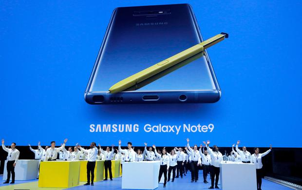 Samsung employees wave from stage beneath an image of the new Samsung Galaxy Note 9 during a product launch event in Brooklyn, New York, U.S., August 8, 2018. REUTERS/Lucas Jackson