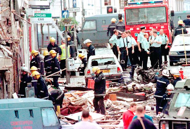 Police officers and firefighters inspect the damage caused by a bomb explosion in Market Street, Omagh. Picture: PA