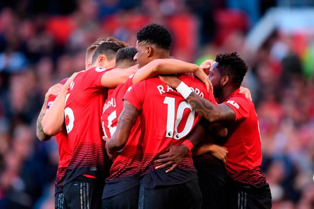 Paul Pogba of Manchester United (hidden) celebrates with team mates after scoring his team's first goal