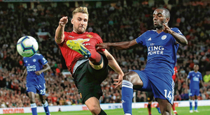 Luke Shaw scores Manchester United's second goal, the first of his senior career, against Leicester City last night despite the best efforts of Ricardo Pereira. Photo: AP