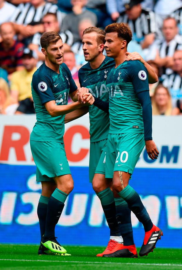 Dele Alli of Tottenham Hotspur celebrates with teammates Harry Kane and Ben Davies after scoring his team's second goal during the Premier League match between Newcastle United and Tottenham Hotspur.