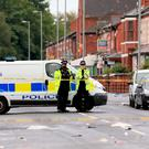 Police officers stand at the cordoned off area in Claremont Road, Manchester, where several people have been injured after a shooting Photo credit: Peter Byrne/PA Wire
